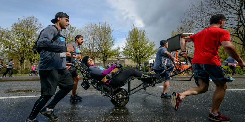 four people helping a physically-disabled man run a race for a charity run