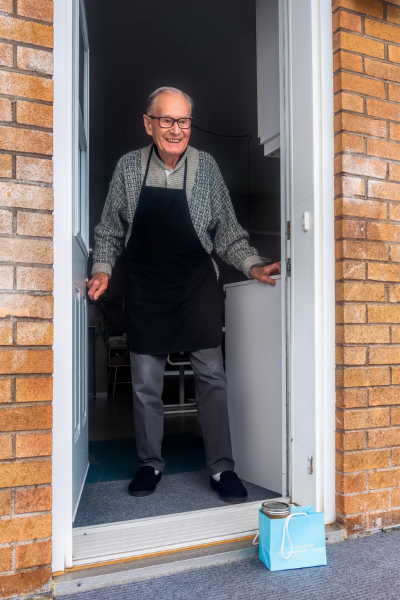 An old man answering the door to find a package