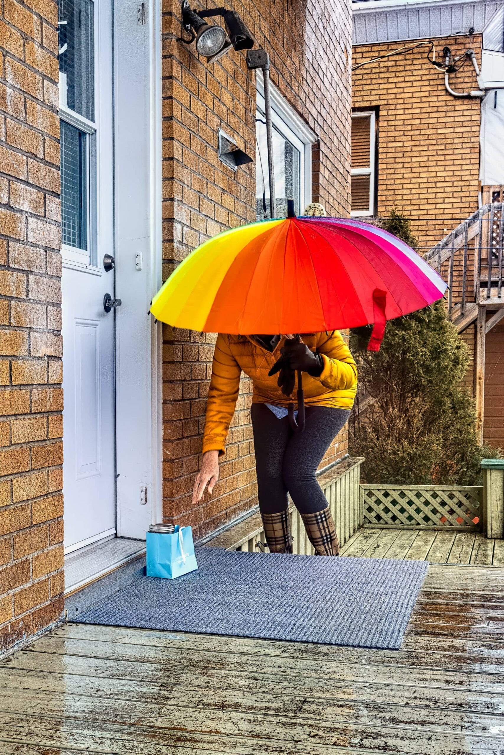 A woman with an umbrella leaving a package outside a door of a house